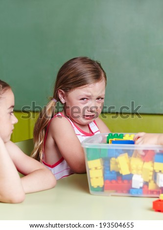 Sad girl crying in a kindergarten group - stock photo