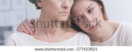 Sad girl embracing her mother with cancer, panorama. - stock photo