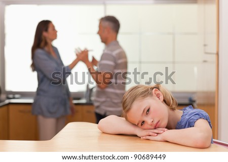 Sad girl hearing her parents arguing in a kitchen - stock photo