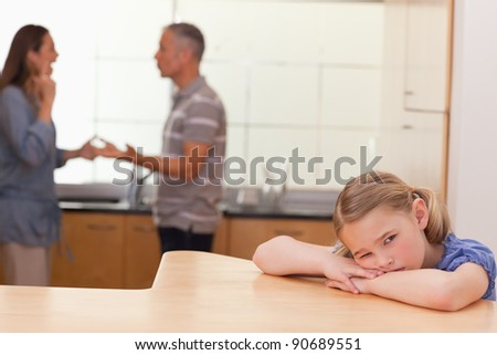 Sad girl hearing her parents fitting in a kitchen - stock photo