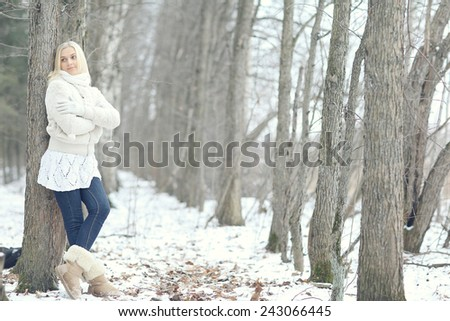 sad girl in a snowy forest - stock photo