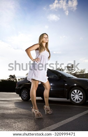 sad girl in a white dress near black car