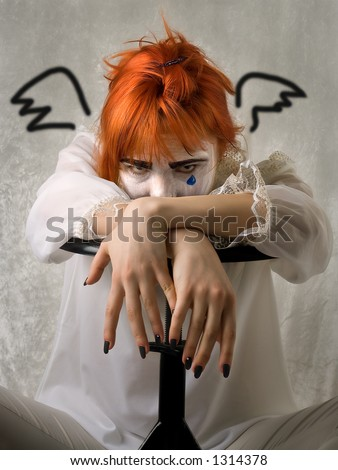 Sad girl in clown makeup with painted wings - stock photo