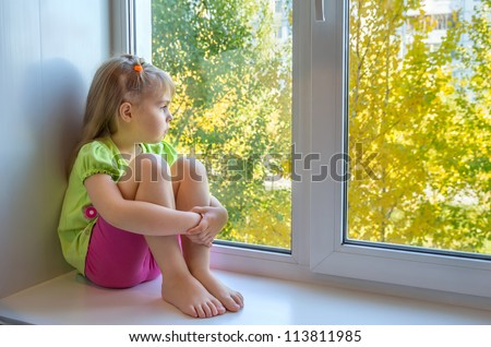 Sad girl in the window - stock photo