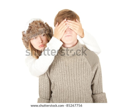 sad girl in winter hat covering her boyfriend's eyes to surprised him