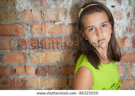 Sad girl is standing in front of a brick wall - stock photo