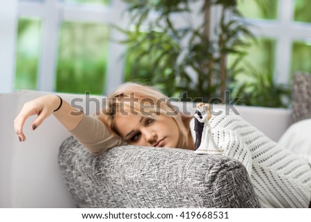 Sad girl laying on bed and looking at wedding topper