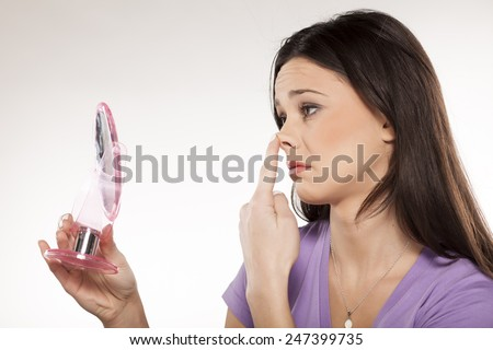 sad girl lifted her nose with the finger in the mirror - stock photo