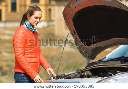 sad girl looking at a broken down car with the hood open - stock photo
