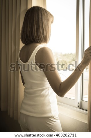 Sad girl looking out of window,vintage filtered.  - stock photo