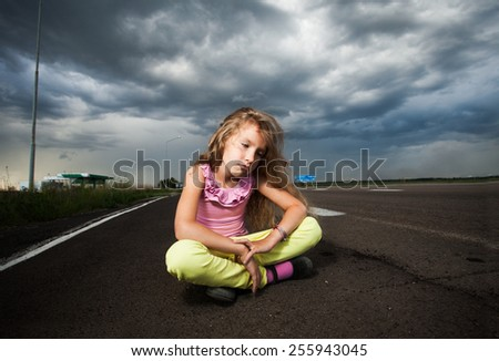 Sad girl near road. Child outdoors - stock photo