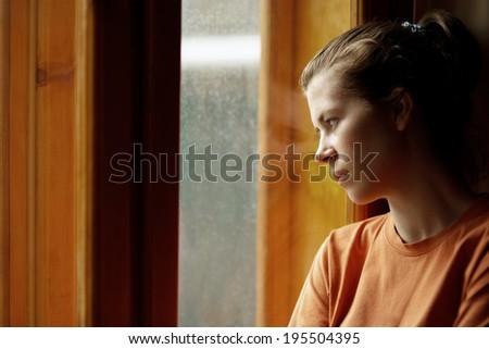 sad girl near window thinking about something - stock photo