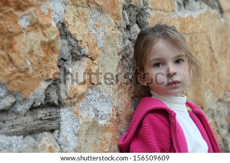 Sad girl on a background of an old wall peeled off