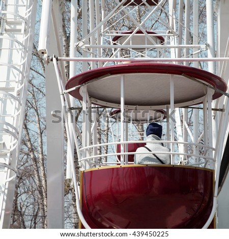 Sad girl on a Ferris wheel at amusement park, winter cold depression. Woman on observation wheel cabin ride close-up at fair - stock photo