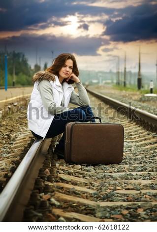 Sad girl on  railway sitting with her suitcase - stock photo