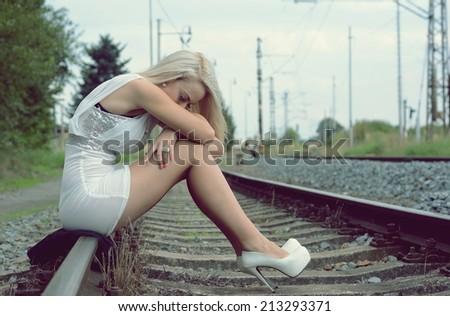sad girl on the rails - stock photo