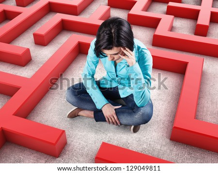 Sad girl sits in a labyrinth with red walls - stock photo