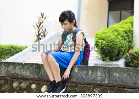 Sad  girl sitting and  thinking in the school - stock photo