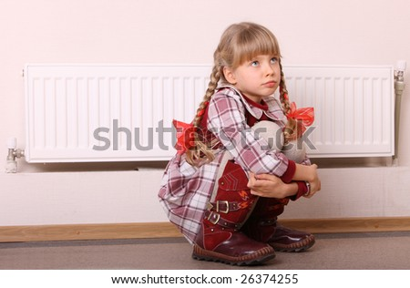 Sad girl sitting near heater. Children depression. - stock photo