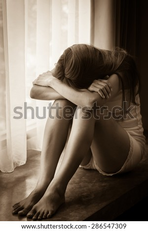 Sad girl sitting near window,sepia filtered. - stock photo