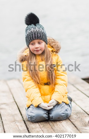 sad girl sitting on a wooden bridge on the river a cloudy autumn day