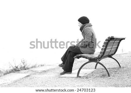 sad girl sitting on park bench - stock photo