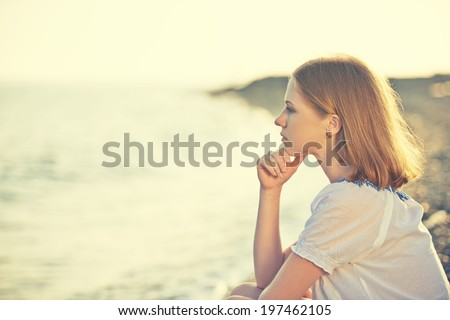 sad girl sitting on the coast on beach and looks into the distance at sea - stock photo