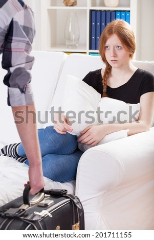 Sad girl sitting on the couch, man leaving - stock photo