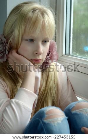 sad girl sitting on the window - stock photo