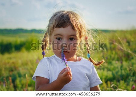 Sad girl sniffing wildflower on a meadow - stock photo
