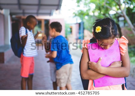 Sad girl standing at school corridor with boys quarreling in background - stock photo