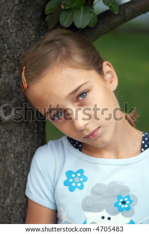 Sad girl under the tree - stock photo