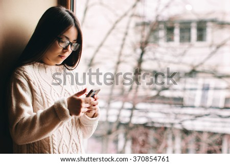 Sad girl wearing eyeglasses and knitted sweater holding a phone and texting at window with copy space