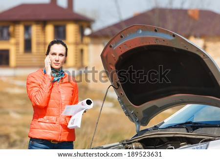 sad girl with a phone in his hand at the car hood open - stock photo