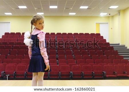 Sad girl with braids and bows stands on stage front of empty auditorium and looks at camera. - stock photo