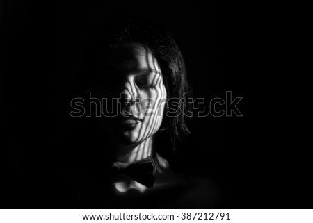sad girl with closed eyes in dark, monochrome