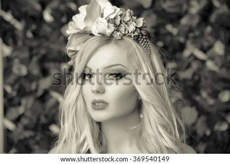 Sad girl with flowers on her head, portrait shot - stock photo
