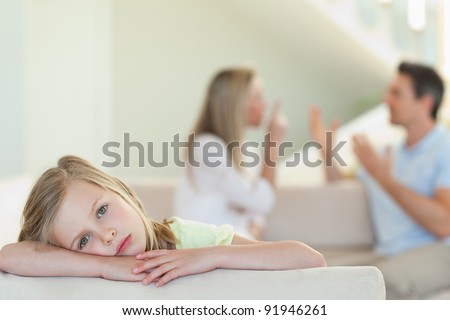 Sad girl with her fighting parents in the background - stock photo