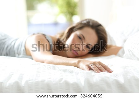 Sad girlfriend missing her boyfriend touching with her hand the empty side of the bed - stock photo