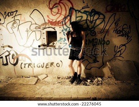 Sad gothic girl in dirty wall - stock photo
