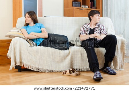 Sad guy and girlfriend after quarrel  in living room at home. Family quarrel - stock photo
