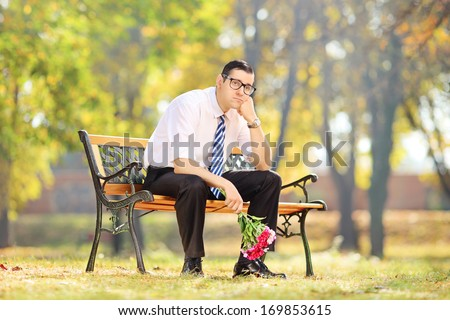 Sad guy holding a bouquet of flowers on a wooden bench in a park - stock photo
