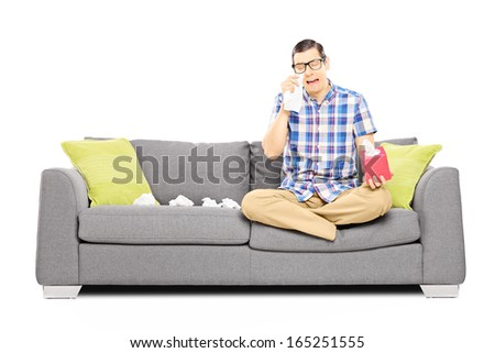 Sad guy sitting on a modern couch and wiping his eyes from crying isolated on white background - stock photo
