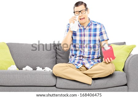 Sad guy sitting on a sofa and wiping his eyes from crying isolated on white background - stock photo
