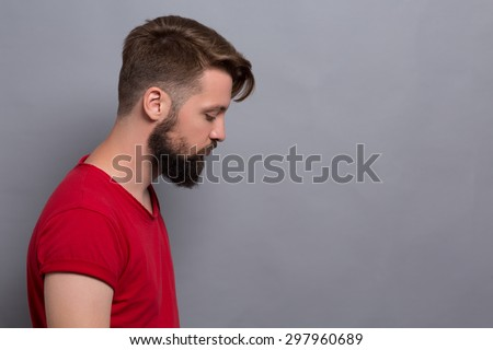Sad hipster bearded man isolated on grey background. Short-haired man in red T-shirt made in profile looking somewhere below. - stock photo