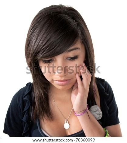 Sad Hispanic girl with hand on chin on white background - stock photo