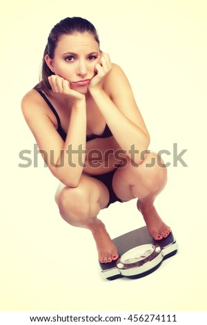 Sad isolated weight loss woman on scale - stock photo