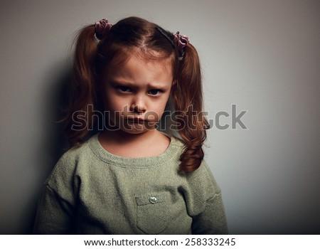 Sad kid girl with long hair looking. Closeup vintage portrait - stock photo