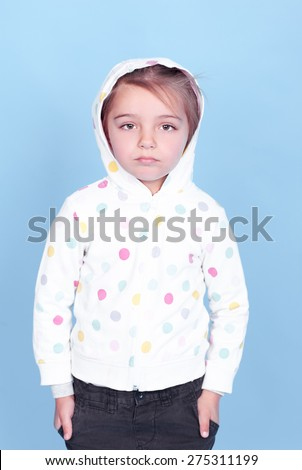 Sad kid girl 3-4 year old wearing sporty hoodie over blue. Childhood. Looking at camera. - stock photo