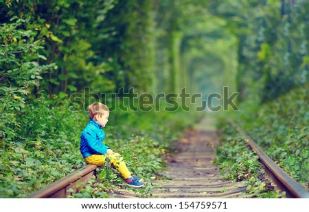 sad kid sitting on rails in green tunnel - stock photo